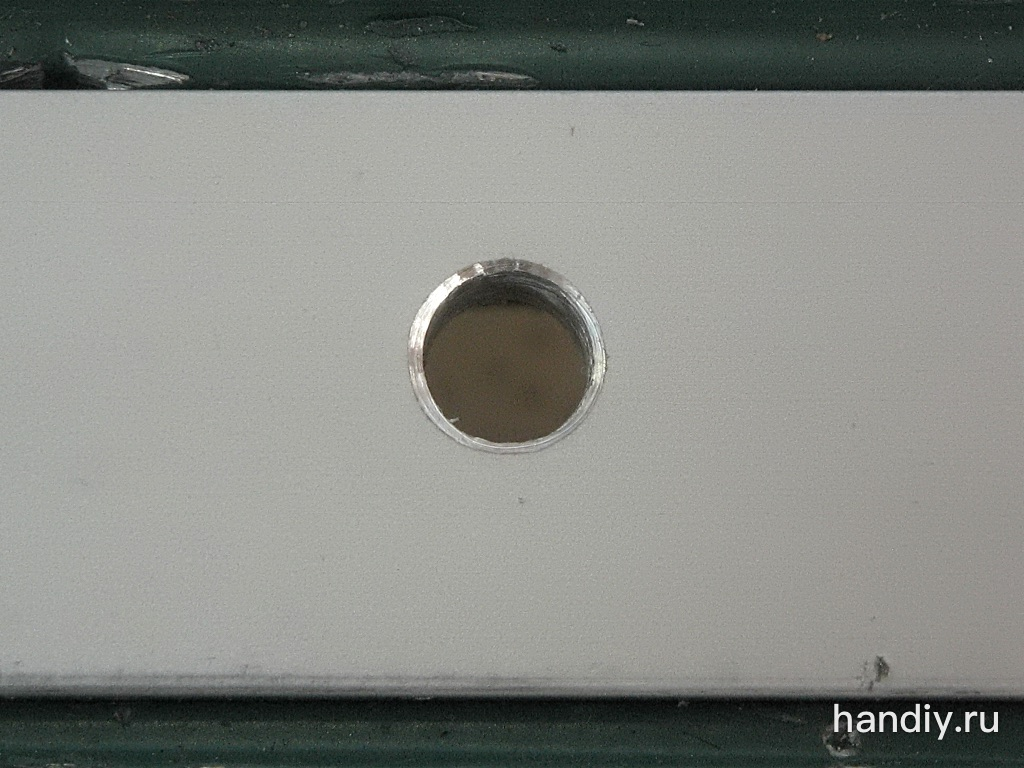 Алюминиевая полоса зажата в тиски. Диаметр просверленного отверстия 5,5 мм. Зенкером снял фаску